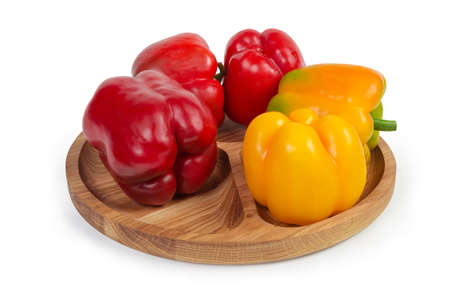 Fresh red and yellow bell peppers on the wooden compartment dish on a white background