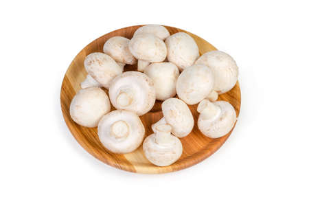Fresh cultivated common button mushrooms on the wooden dish on a white background