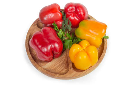 Fresh red and yellow bell peppers and greens on the wooden compartment dish on a white background