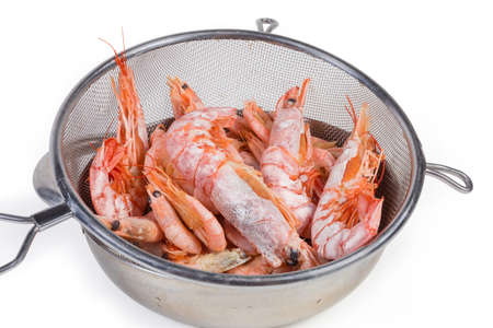Boiled king prawns and usual shrimps in the round stainless steel sieve on metal bowl close-up on a white bsckground