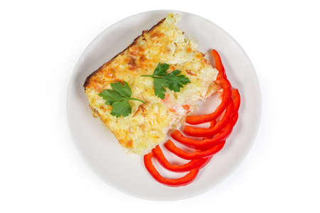 Serving of the gratin made with cauliflower, shrimps, cheese and breadcrumbs, slices of fresh bell peper on the white dish on a white background, top view
