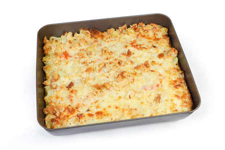 Baked gratin made with cauliflower, shrimps, cheese and breadcrumbs in the metal oven tray on a white background