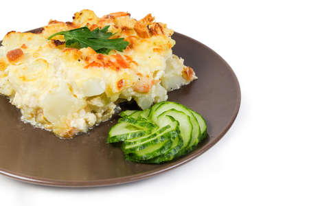 Serving of the gratin made with cauliflower, shrimps, cheese and breadcrumbs, slices of fresh cucumber on the brown dish on a white background, fragment close-up in selective focus