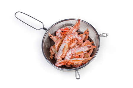 Boiled king prawns and usual shrimps in the round stainless steel sieve on metal bowl on a white bsckground  스톡 콘텐츠