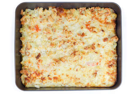 Baked gratin made with cauliflower, shrimps, cheese and breadcrumbs in the rectangular metal oven tray on a white background, top view  스톡 콘텐츠
