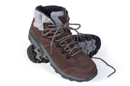 Pair of brown leather trekking boot on a white background, view from the toes side