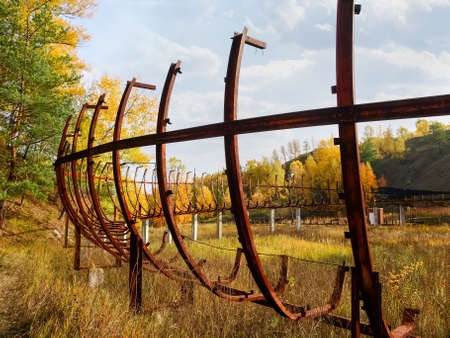 Remains of steel framework of the old abandoned wooden luge track among dry withered grass in autumn, Ukraine