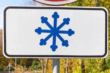 Additional plate to the road sign with snowflake image for warning about risk of snow and ice, set below the main traffic sign Stock Photo