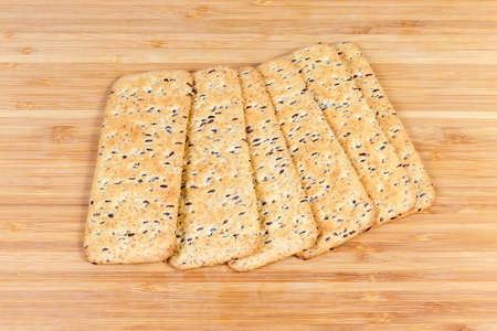 Crisp savory cookies made with whole flax seeds addition on the wooden surface