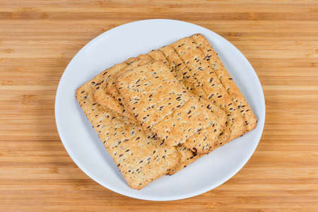 Crisp savory cookies made with whole flax seeds addition on white dish on the wooden surface, top view