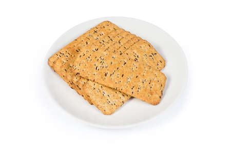 Crisp savory cookies made with whole flax seeds addition on the white dish on a white background