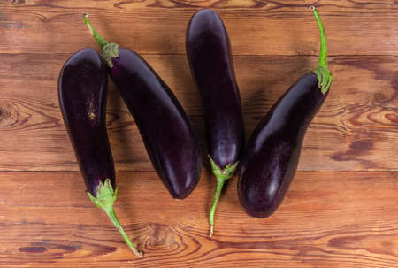 Fresh uncooked purple eggplants on the old rustic table, top view