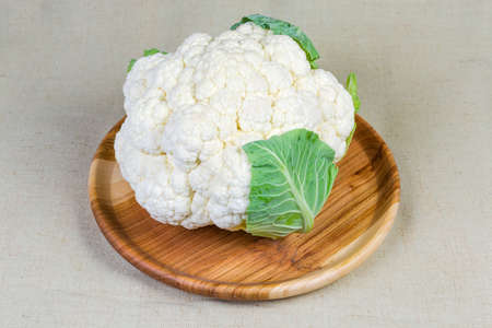 Head of the fresh cauliflower with some leaves on the rustic wooden dish on cloth surface 写真素材