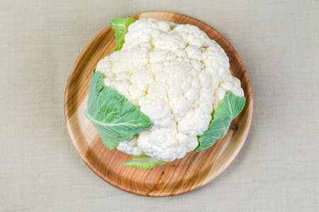 Head of the fresh cauliflower with some leaves on the rustic wooden dish on cloth surface, top view