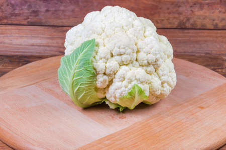 Head of the fresh cauliflower on the round wooden serving board close-up in selective focus