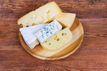 Pieces of various soft cheese with white and blue mold, medium-hard cheese and Swiss-type cheese on the wooden dish on the old rustic table