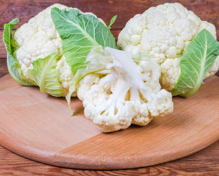 Two whole heads with some leaves and separate branch of fresh cauliflower on the round wooden serving board on the rustic table