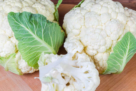 Fragment of the whole heads with some leaves and separate branch of fresh cauliflower on the wooden surface, background 写真素材
