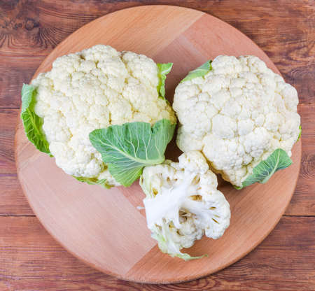 Two whole heads with some leaves and separate branch of fresh cauliflower on the round wooden serving board on the rustic table, top view