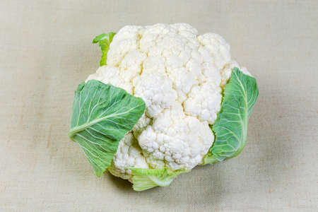 Head of the fresh cauliflower with some leaves on the cloth surface