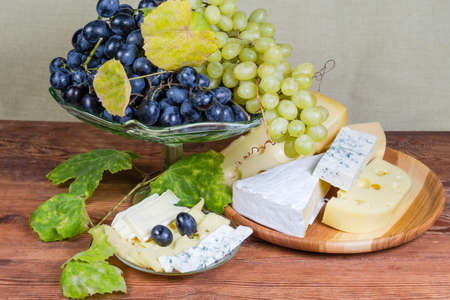Pieces and slices of various cheese varieties against blue and white grape on the vintage glass fruit vase and vine autumn leaves on the old rustic table