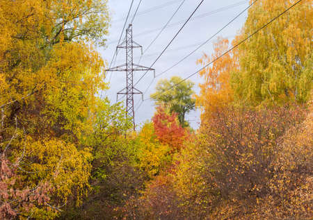 Steel lattice transmission tower of overhead power line over of the trees with autumn leaves on a background of cloudy sky