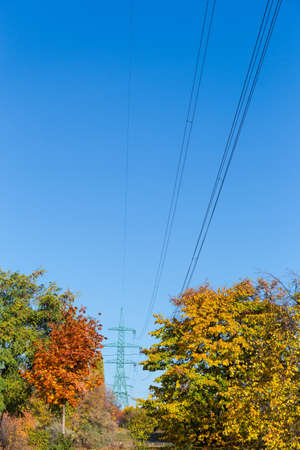 Overhead power line equipped with steel lattice transmission towers over the autumn trees against clear sky