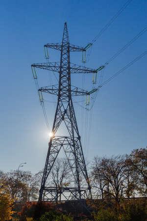 Steel lattice tower of overhead power lines over the autumn trees against clear sky and sun Stok Fotoğraf