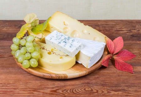 Various cheese with white and blue mold, medium-hard cheese and Swiss-type cheese, white sultana grapes on the wooden dish, vine autumn leaves on the old rustic table