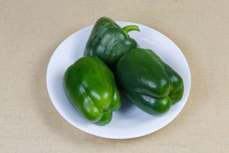 Whole fresh raw green bell peppers on white dish on the cloth surface