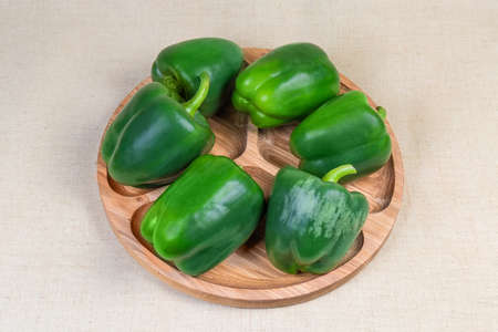 Whole fresh raw green bell peppers on the wooden compartment dish on the cloth surface Stok Fotoğraf