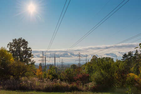 Several overhead power lines equipped with transmission towers of various designs over the trees and other vegetation against sky with sun in autumn Stok Fotoğraf