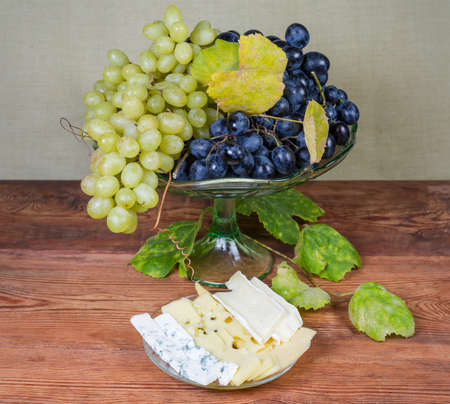 Slices of various cheese varieties on the saucer, blue grape and white sultana grape with vine autumn leaves on the vintage glass fruit vase on the old rustic table