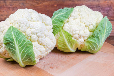 Two heads of the fresh cauliflower with some leaves on the round wooden serving board on the rustic table