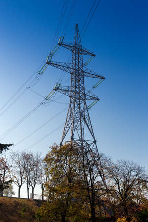 Steel lattice tower of overhead power lines over the autumn trees against clear sky