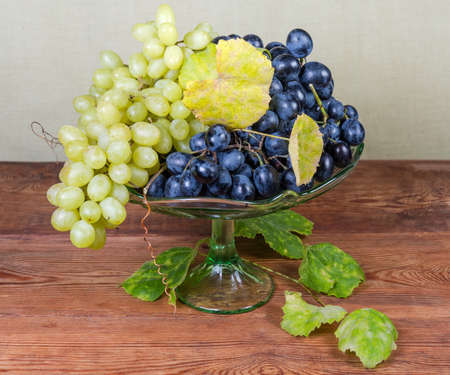 Clusters of the ripe white Sultana grape and blue grape with autumn vine leaves and tendrils on green glass vintage fruit vase on the old rustic table