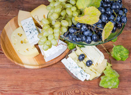 Clusters of blue and white sultana grapes on the vintage glass fruit vase against pieces of different varieties of cheese on the old rustic table, top view
