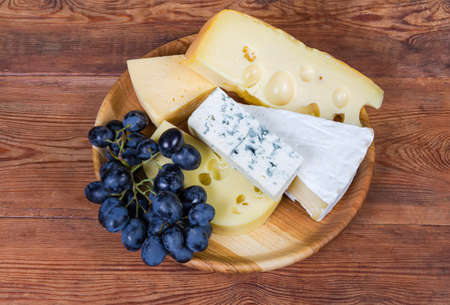 Pieces of various soft cheese with white and blue mold, medium-hard cheese and Swiss-type cheese, cluster of blue grapes on the wooden dish on the old rustic table
