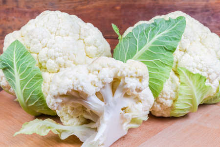 Whole heads with some leaves and branch of fresh cauliflower on the wooden surface close-up in selective focus Stok Fotoğraf