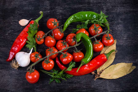 Cherry tomatoes, chili peppers, garlic, greens twigs and dry bay leaves on the black surface, top view, background  Stock Photo