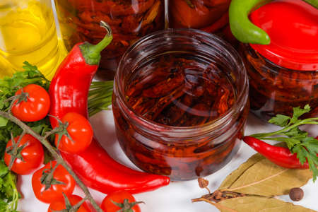 Sun-dried red tomatoes preserved in olive oil in small open glass jar among ingredients close-up in selective focus