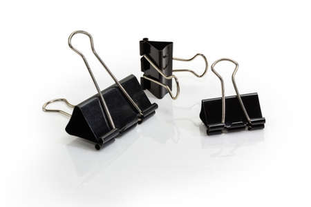 Black paper binder clips different sizes on a white reflecting background