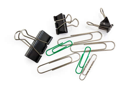 Binder paper clips and traditional steel wire paper clips oblong looped shape different sizes on a white background, top view