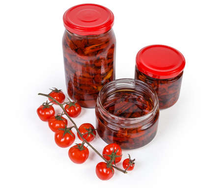Sun-dried red tomatoes preserved in olive oil in different small glass jars and claster of fresh cherry tomatoes on a white background