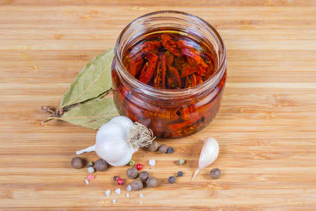 Sun-dried tomatoes preserved in olive oil in open small glass jar among spices on the wooden surface
