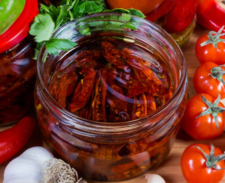 Sun-dried red tomatoes preserved in olive oil in open small glass jar among fresh vegetables close-up in selective focus Stock Photo