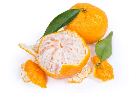 One partly peeled and one unpeeled mandarin oranges, peel and leaves close-up on a white background