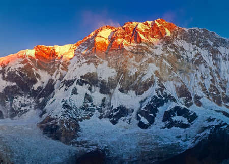 Central part of south face of Annapurna I Main Mount partially sunlit at sunrise on a background of clear sky in the Himalayas, Nepal