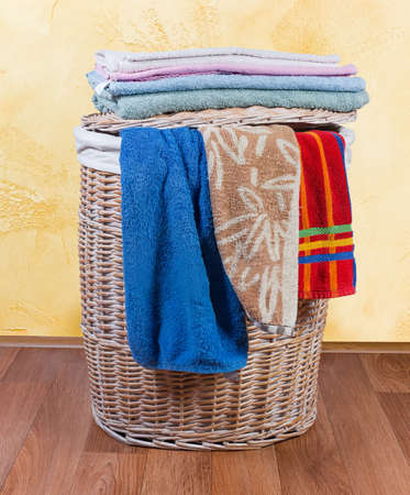 Wooden wicker laundry basket standing on the floor, different home bath and hand towels lie and hanging on her