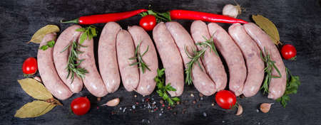 Uncooked pork sausages for grilling in natural casing among the some vegetables, greens and spices on the dark surface, top view